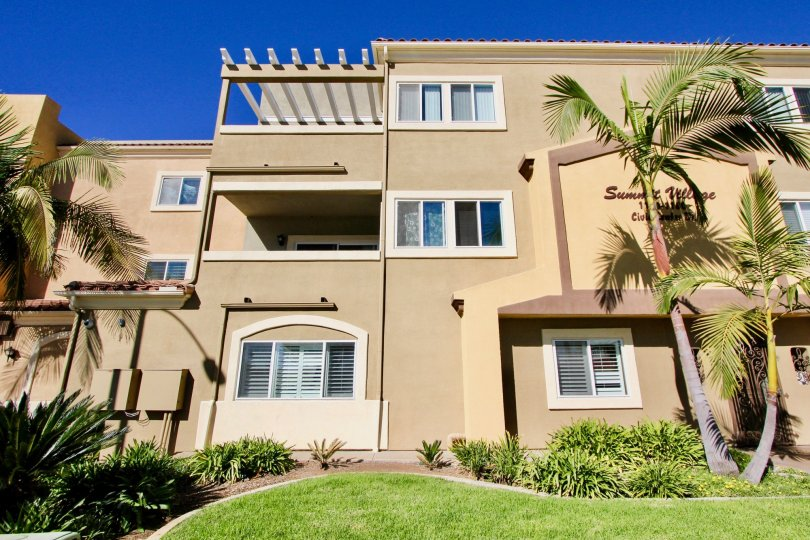 Cloudless blue skies overlooking Summit Village apartment homes with lush grass and palm trees.