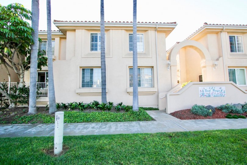 Well manicured lawns and tall palm trees and arched entryway at Villa Pacific
