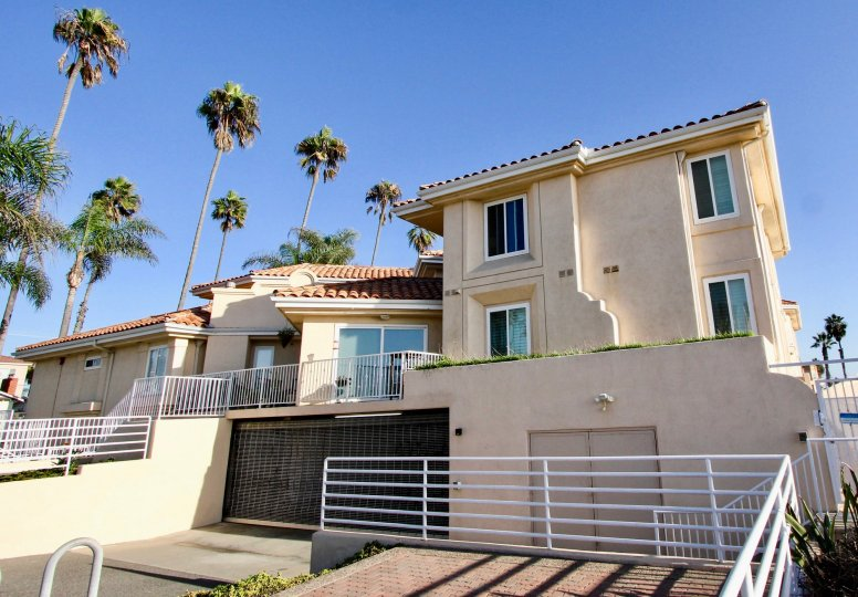 The Villa Pacific in Oceanside California is flanked by tall palm trees around its property.