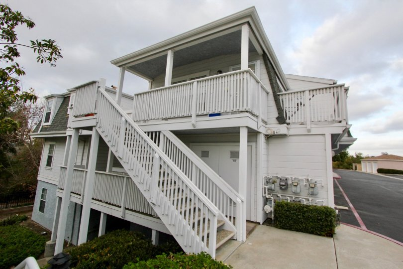 White three story home with multiple balconies and stairs, located in Villa San Luis Rey, Oceanside, California.