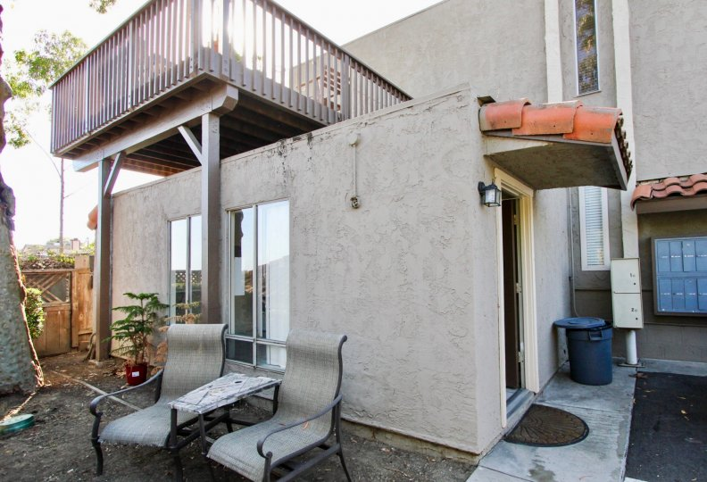 Building with second floor balcony, two chairs and gate beside it, located in Vine Villas, Oceanside, California.