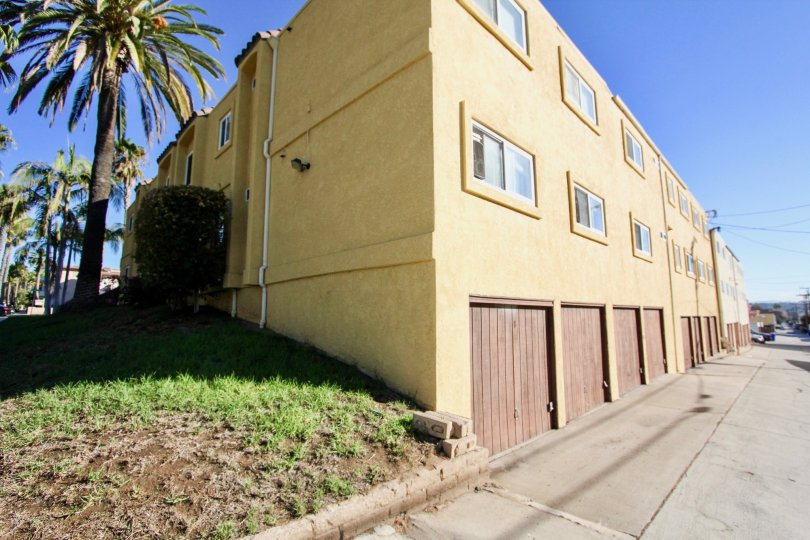 A sunny day in the area of 1915 Emerald, condos, garages, parking lot, palm trees
