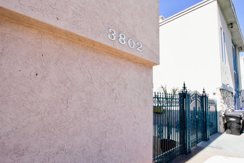 A pointy black gate between a pink building & a whie building at 3802 Riviera Condos in Pacific Beach CA
