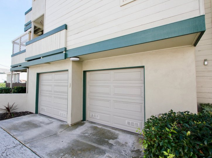 2 garage doors for a multi-story building with bushes on the right and a succulent plant on the left