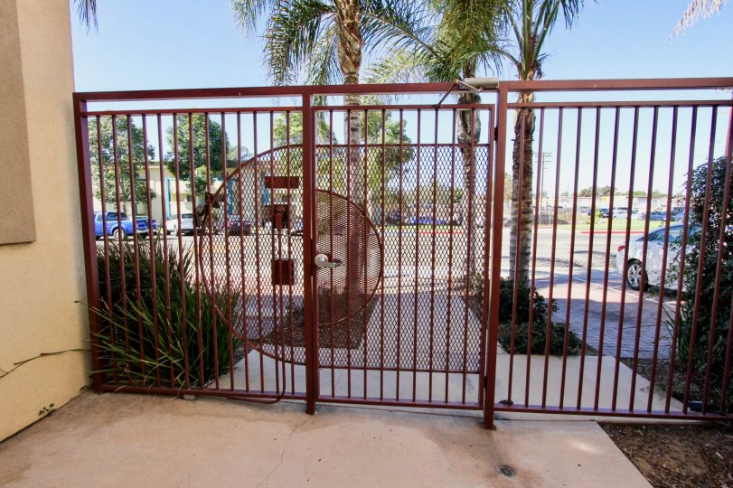 THIS IMAGE SHOWS THAT STEEL GATE WHICH HAS BEEN CAR PARKING, TREES, PLANTS