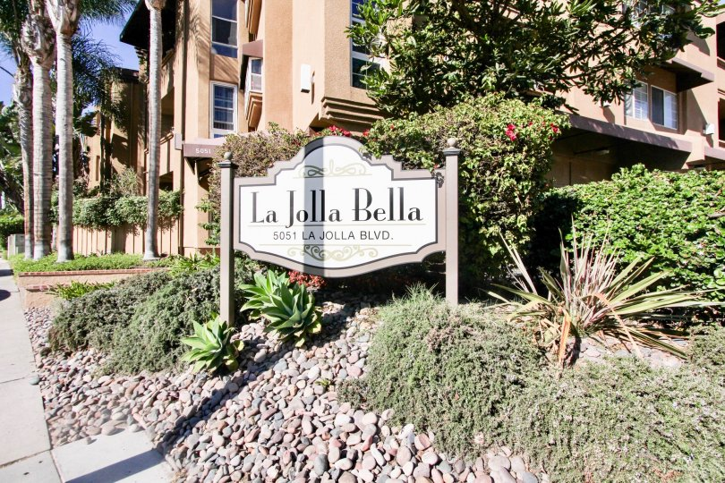 sign of La Jolla Bella welcoming nto the community with lush geenery and housing behind it