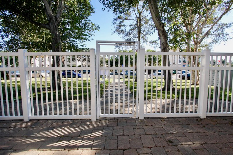 A sunny day in the area of Loring Manor, outside, brick walkway, fence, white, trees, cars