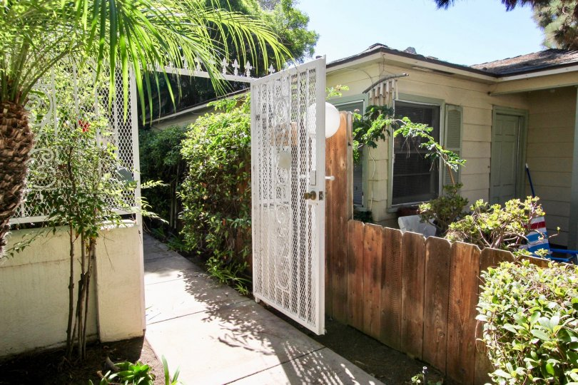 An entrance with a white open gate in the Oliver Avenue Condos community.