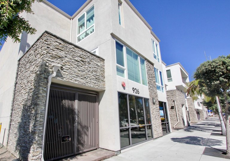 A contemporary townhouse in the Pacific Beach Sands community with stone cladding and grayish paint.