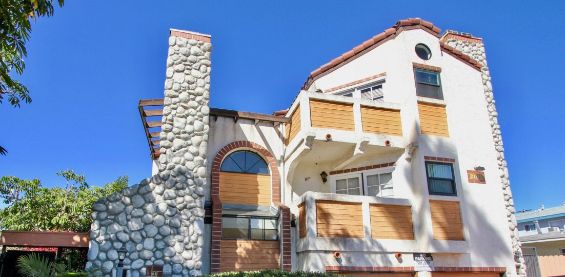 Rock chimney and wood siding on white stucco at Pacific Gardens II in Pacific Beach, California