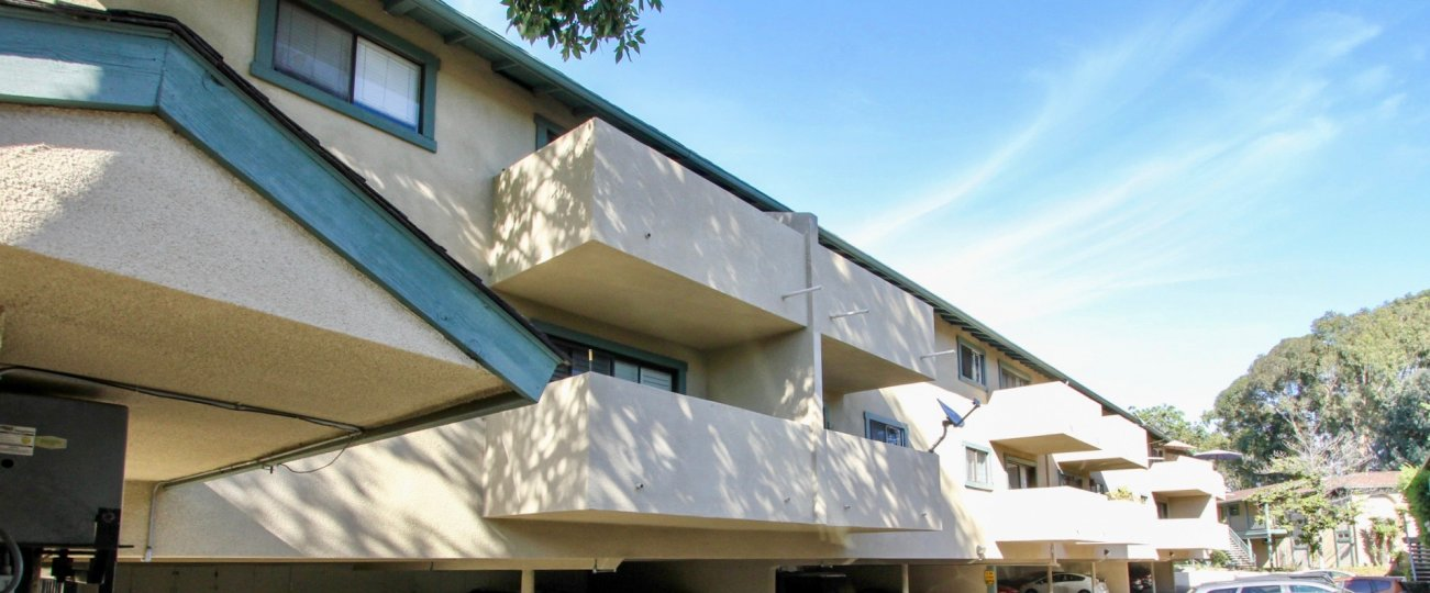 A sunny day in the area of Pacific Woodlands, outside, balconies, condos, tree, car