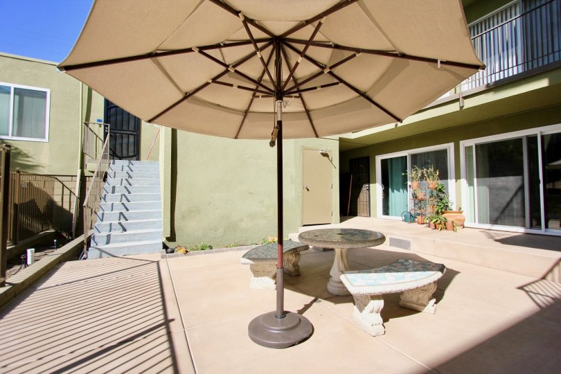 Umbrella next to a cement bench that is surrounded by condos in Regency Condos at Pacific Beach CA