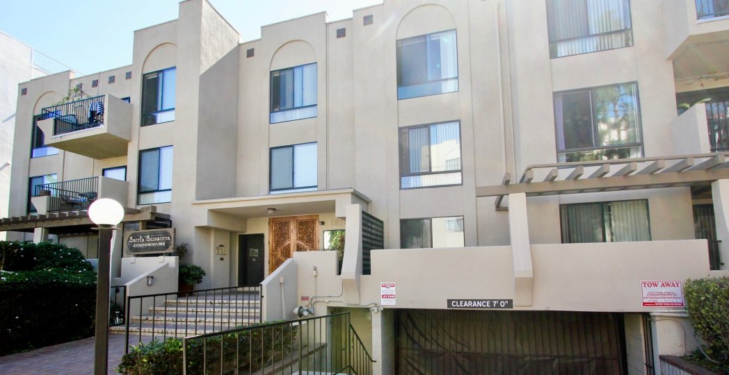 A sunny day in the area of Santa Susanna, outside, railing, stairs, door, light post, condos