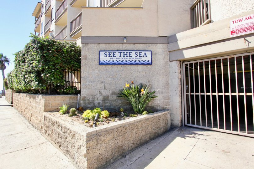 The side of See The Sea apartments and potted plants in front of the sign.