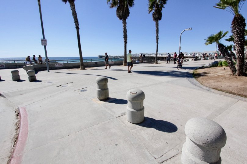 Cement posts on the sidewalk with people at See the Sea, Pacific Beach, California