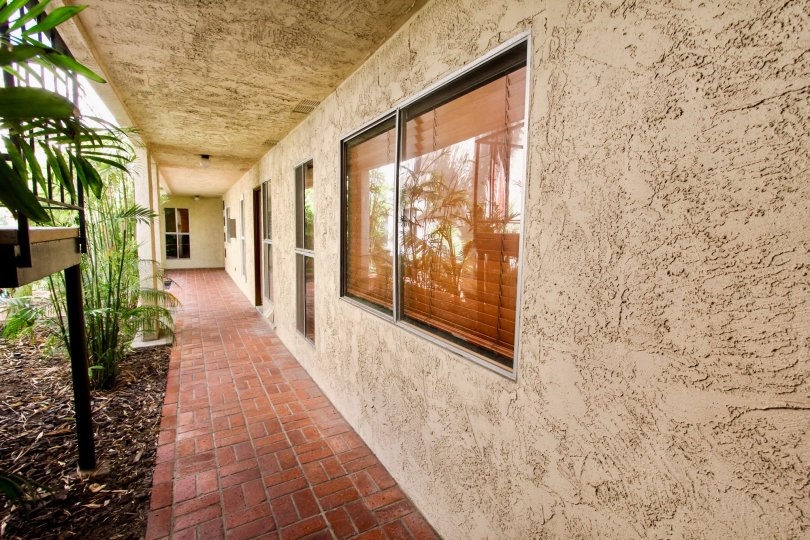 A tiled hallway with stucco walls and sliding windows in the Shasta Daisy community.