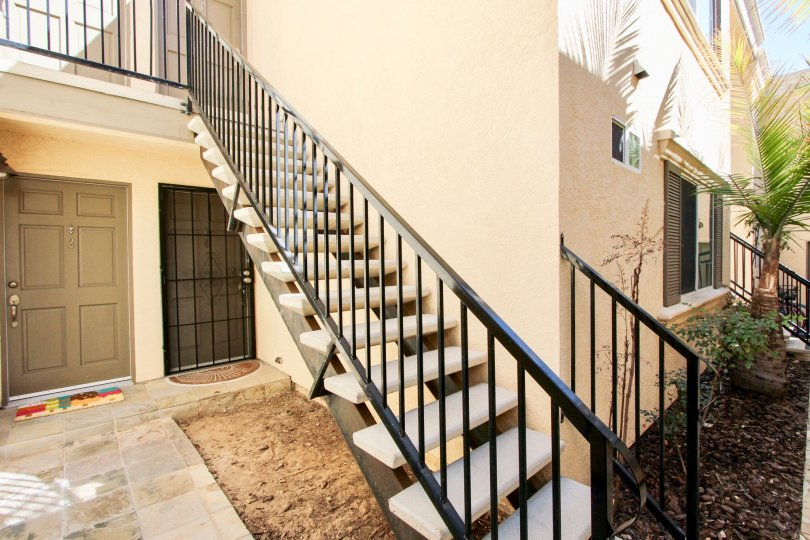 An exterior staircase in theThomas Avenue Condominiums above a bare soil.