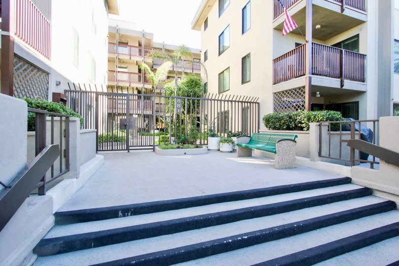 An entryway with a gray gate and a green bench in the Turramurra Condominiums.