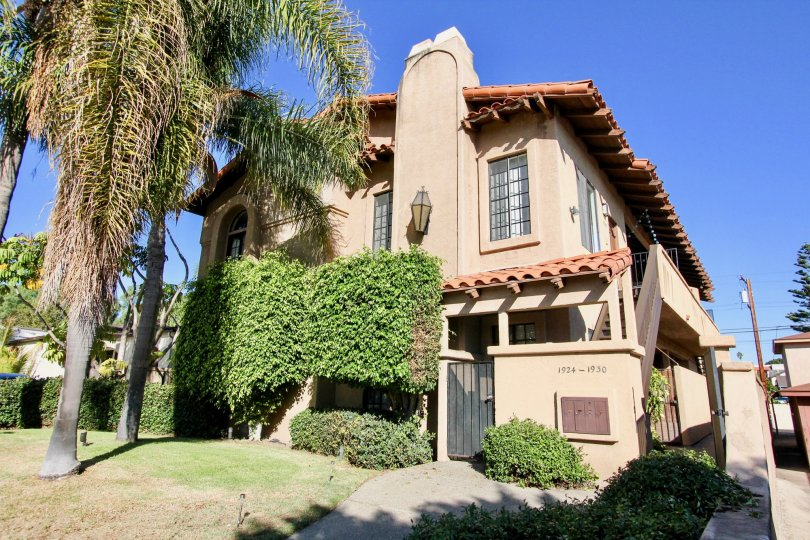 A two-storey traditional residence with a tall shrub and pine tree in the Vista Adelle Mar community