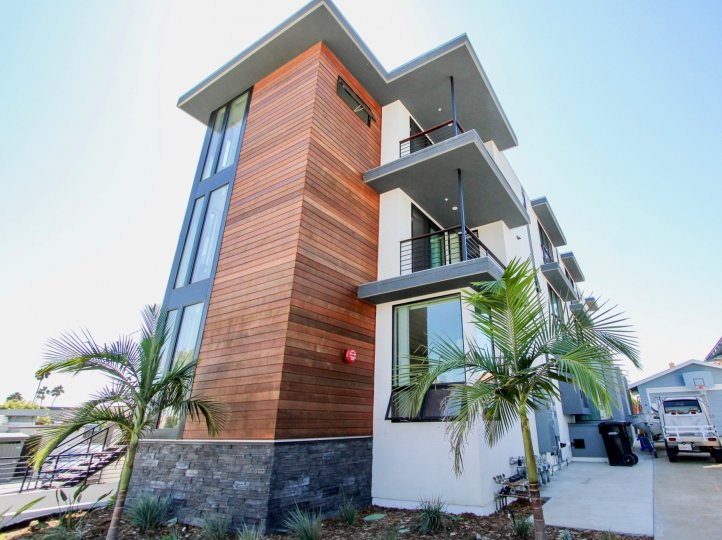 Modern exterior styling with wood siding and horizontal iron railings at the Carleton