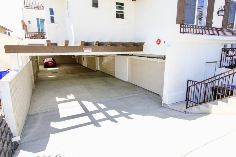 Underground parking entrance with overhead pergola and decorative shutters at Keats Place in Point Loma, CA