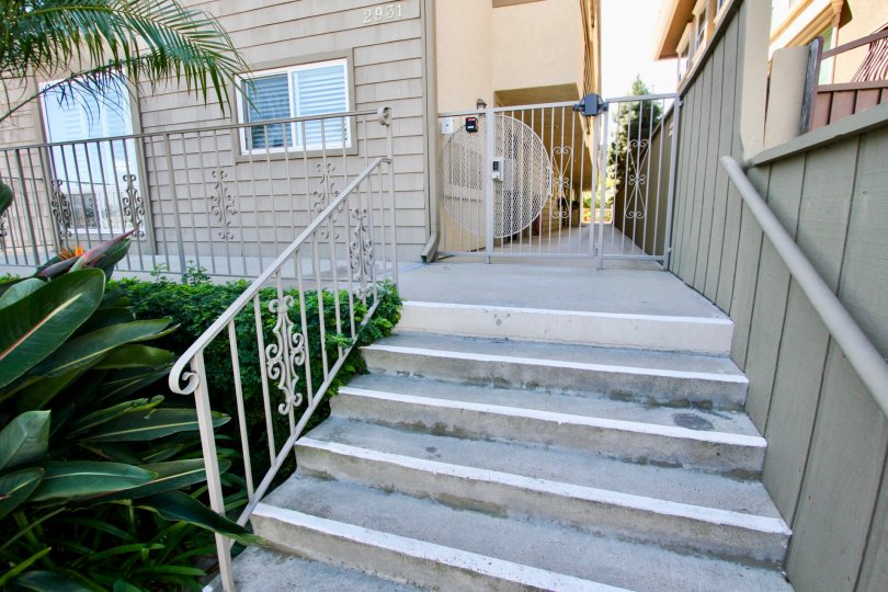 Small stairs leading to balcony with door and gated path, located in La Playa Bayshore, Point Loma, California.