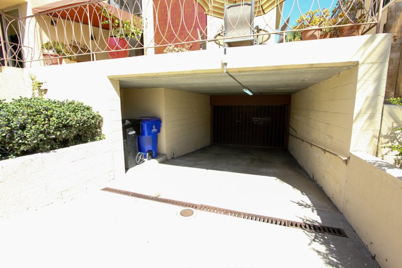 View of garage and waste storage beneath terrace at La Playa Plaza in Point Loma, CA