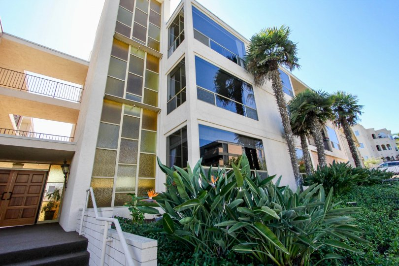 A three story condominium building with a glass wall at Park La Playa in Point Loma CA
