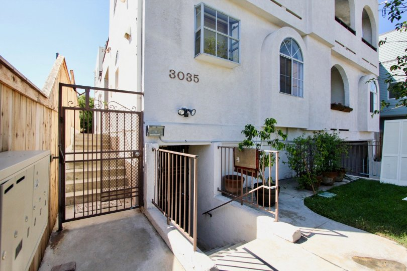 A wooden privacy fence shifts up as the sidewalk ascends with stairs at Primrose Villas