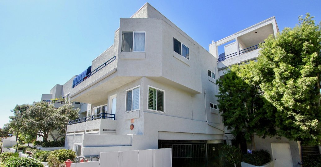 three story white condominiums with dark parking area inside vista la playa at point loma ca