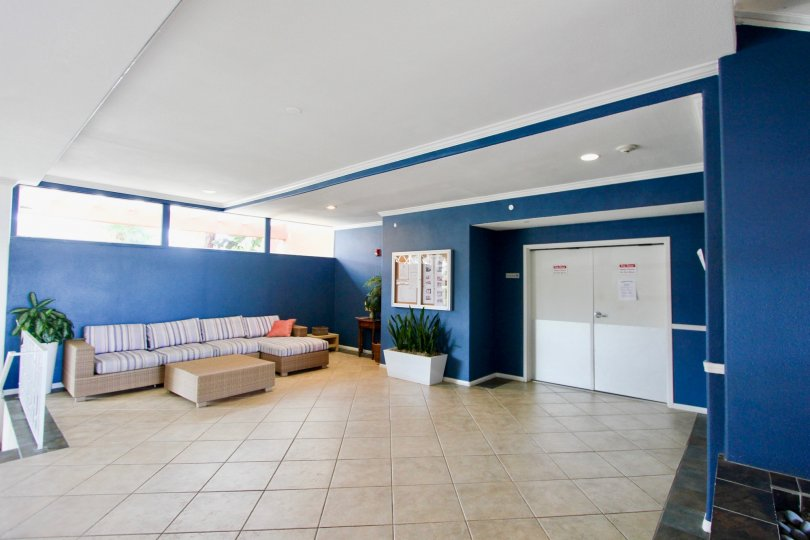 Blue interior of modern lobby with couch and white double doors in Yacht Club Condos