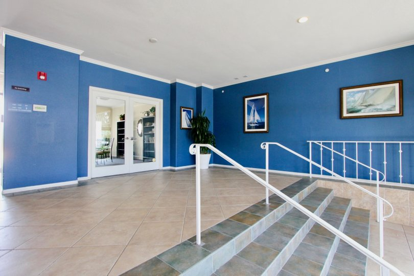 Nautical themed entrance foyer with framed art and tile floors at Yacht Club Condos