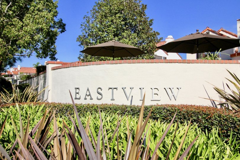 "A sign saying ""Eastview"" with some bushes and trees around it and shade umbrellas and houses in the back during a sunny day in Eastview, Rancho Bernardo, CA"