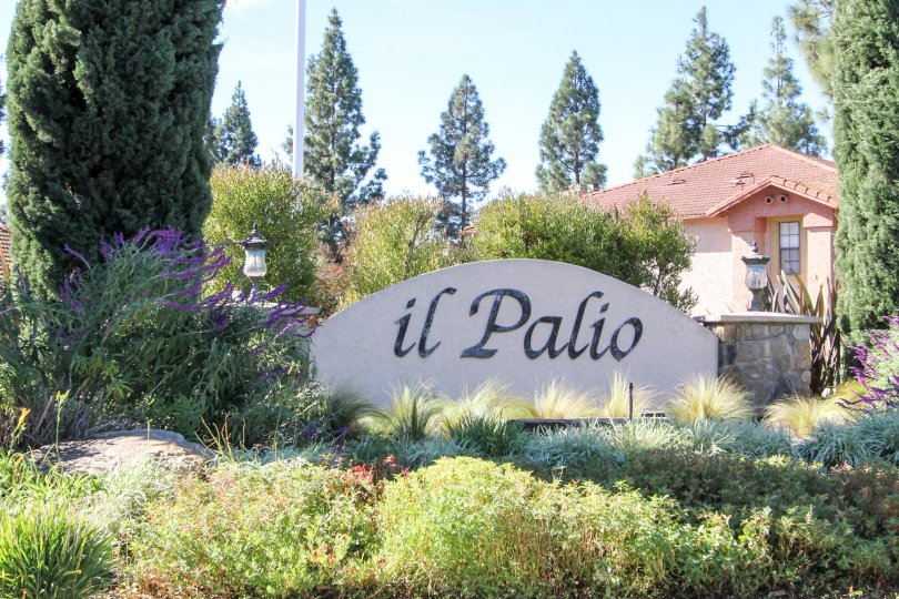 Black writing on a white sign surrounded by plants at II Palio in Rancho Bernardo CA