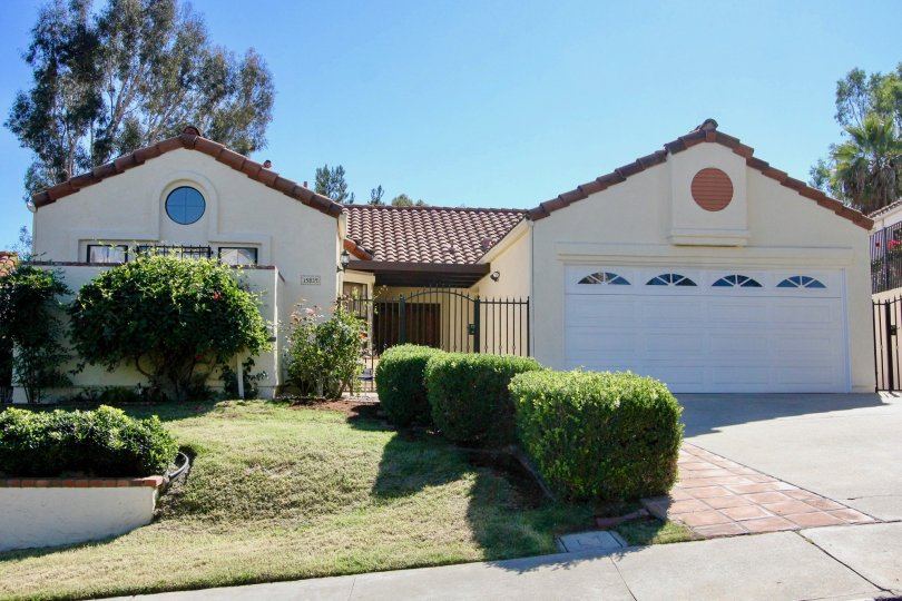 A beige house with a white garage and some bushes in front during a sunny day in Las Brisas, Rancho Bernardo, CA