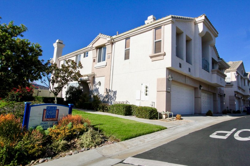 Two story residential building near yard and blue sign at Mira Lago in Rancho Bernardo CA
