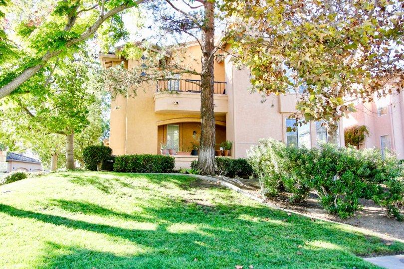 Orange condo building with lots of trees and grass inside Morada in Rancho Bernardo CA