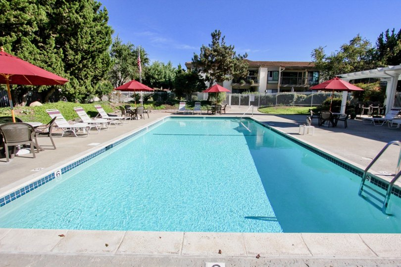 A suuny day in One Oaks North has swimming pool and seating chairs for mind relax