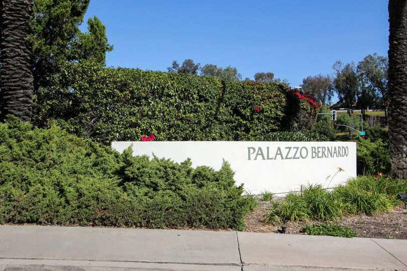 Sidewalk and lush greenery surrounding signage in front of the Palazzo Bernardo in California community.