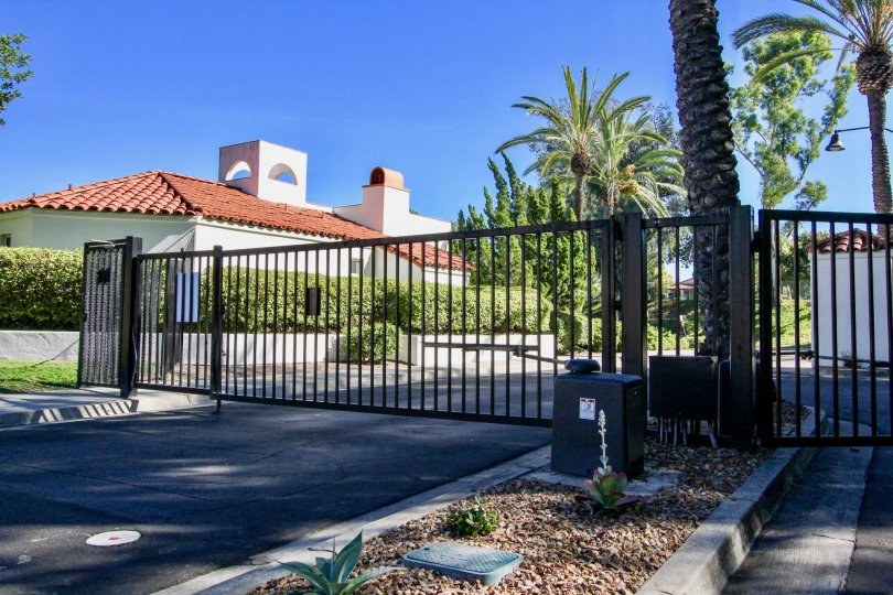 A gate with some palm trees and a house in the background during a sunny day at Palazzo Bernardo, Rancho Bernardo, CA