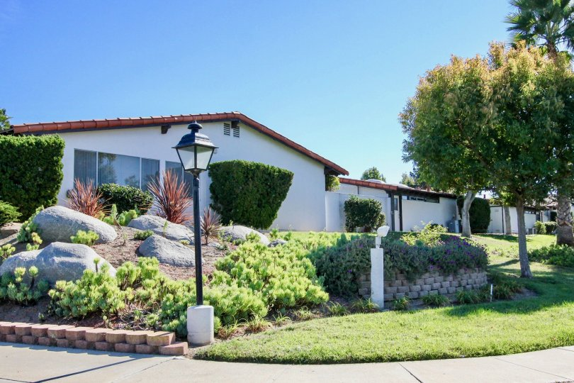 A one story home with landscaping and a lamp post in Seven Oaks Haciendas