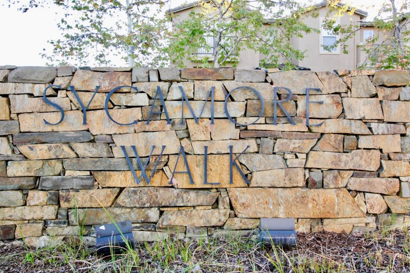 Black iron sign on stone wall near residence at Sycamore Walk in Rancho Bernardo CA