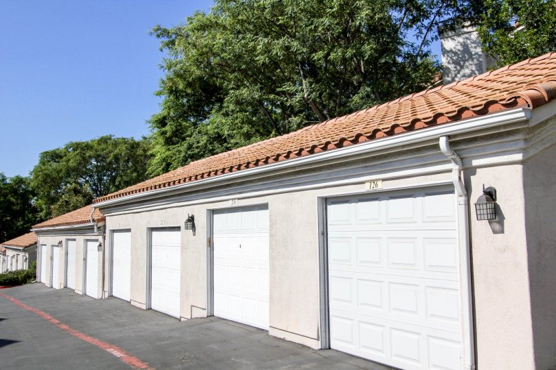 Single car garage units on a gentle sloping back lane with spanish inspired roofs in San Marcos