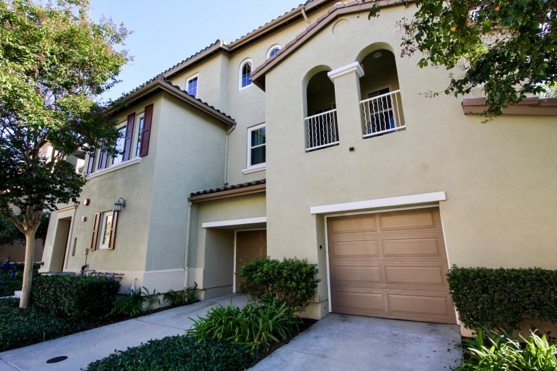 A three-storey residence with brown garage doors and olive walls in Calico Bluffs neighborhood