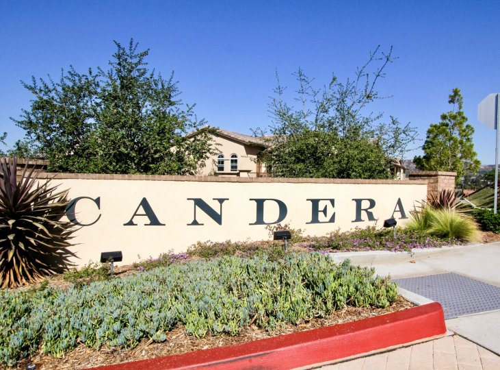 The front entrance sign of the Candera subdivision with landscaping under a clear blue sky.