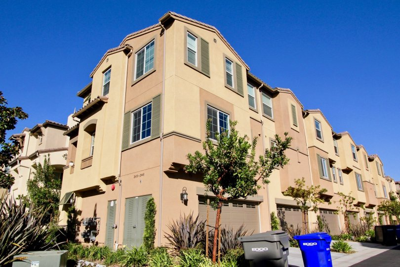 Three story brown units with garages in Laurel at San Marcos CA