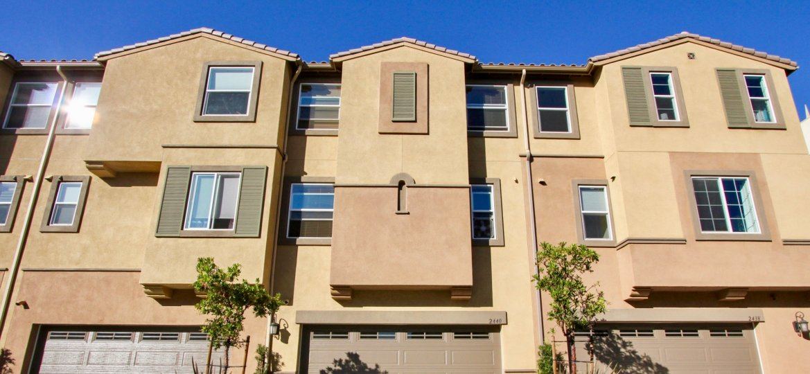 Three story home with large brown garage doors in Laurel at San Marcos CA
