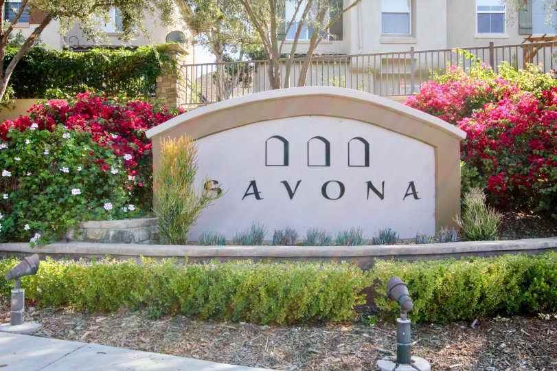 Lights point toward the community sign in front of a fence at the Savona residential building