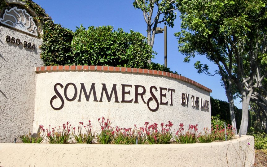 Black letters on a cement wall with red bricks at Sommerset By The Lake in San Marco CA
