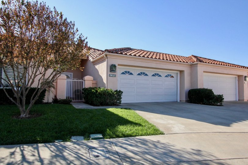 Single story pink homes with white garages inside The Colony in San Marcos CA